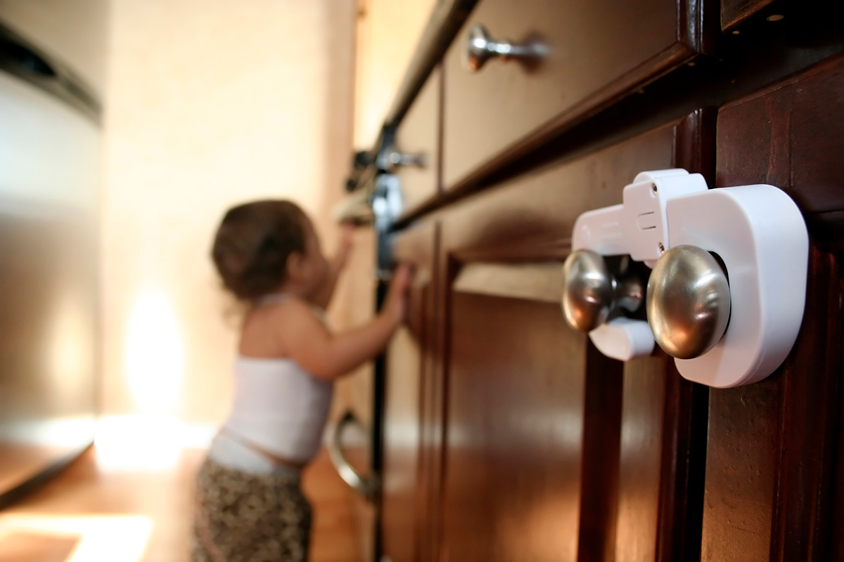 Close up on child proof cabinet latch and knob on far right